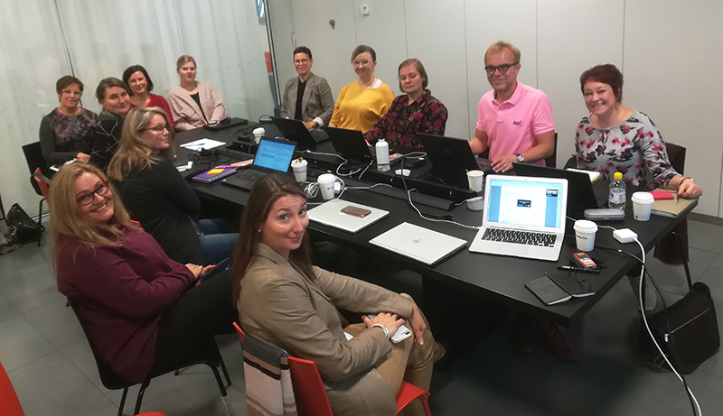 Oiva-hankkeen työtekijät istuvat kokouspöydän äärellä. Päydällä tietokoneita.